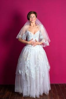 Sposa su sfondo rosa donna vestita in abito da sposa con copyspace in pizzo per il testo