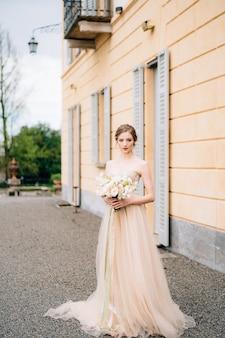Sposa in un abito rosa con un mazzo di fiori in strada