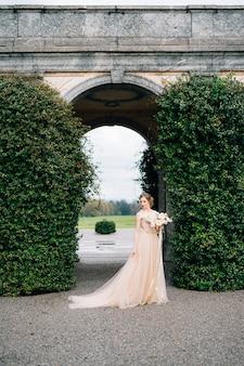 Sposa in un abito rosa con un mazzo di fiori