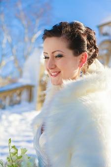 Sposa in posa nella foresta invernale in una pelliccia. sessione fotografica di matrimonio in un parco innevato.