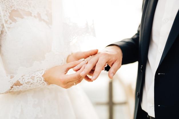 La sposa mette l'anello al dito dello sposo durante la cerimonia nuziale.