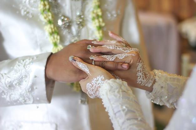 La sposa mette un anello nuziale al dito degli sposi