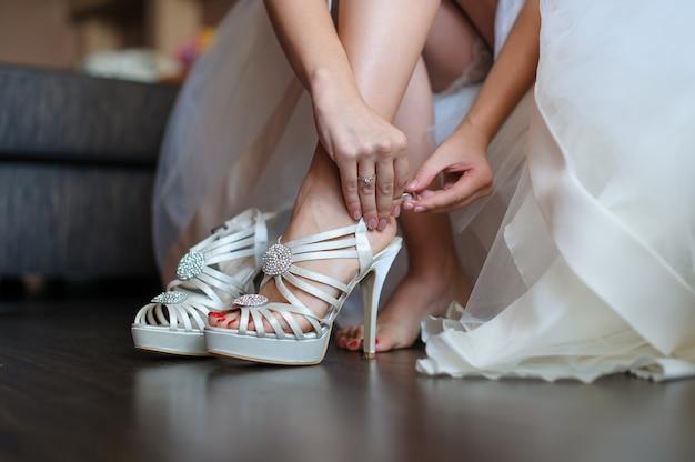 La sposa mette le scarpe bianche per il matrimonio
