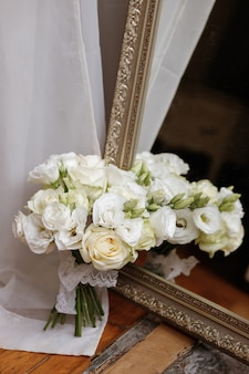 Il bouquet della sposa vicino allo specchio. riflesso del bouquet