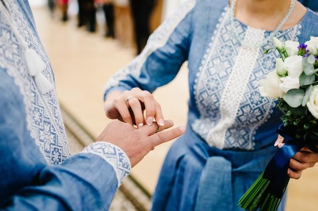 La mano della sposa indossa un anello d'oro di fidanzamento sul dito dello sposo. giorno del matrimonio. mani con fedi nuziali. avvicinamento. sposi ricamati, tradizioni nuziali.