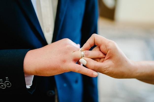 La mano della sposa indossa un anello d'oro di fidanzamento al dito dello sposo. giorno del matrimonio. mani con fedi nuziali. avvicinamento.