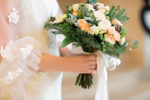 Le mani della sposa tengono un bellissimo bouquet da sposa di rose bianche. fotografia d'arte.