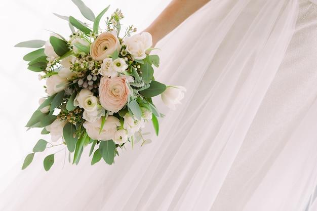 Le mani della sposa tengono un bellissimo bouquet da sposa di rose bianche.