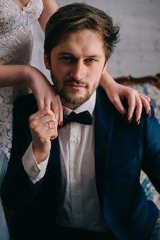 Le mani della sposa giacciono sulle spalle dello sposo che guarda davanti