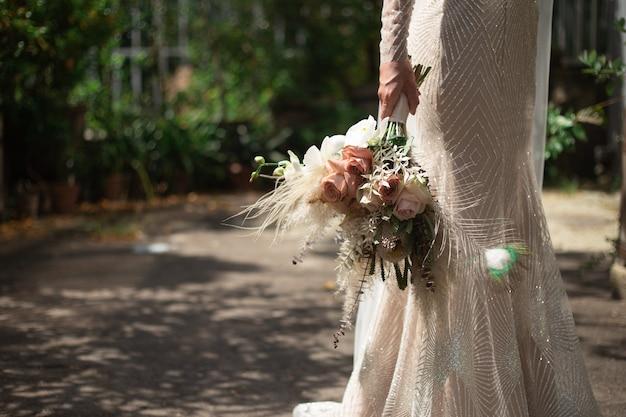 Una sposa in un abito da sposa lucido si alza e tiene in mano un bouquet da sposa in stile boho.