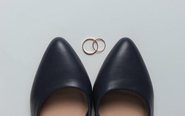 La sposa calza gli anelli di nozze d'oro su uno sfondo bianco