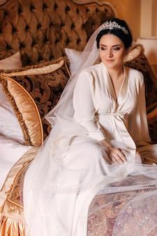 La sposa si siede su un letto elegante tra i cuscini. ragazza in una veste bianca e velo da sposa con diadema.