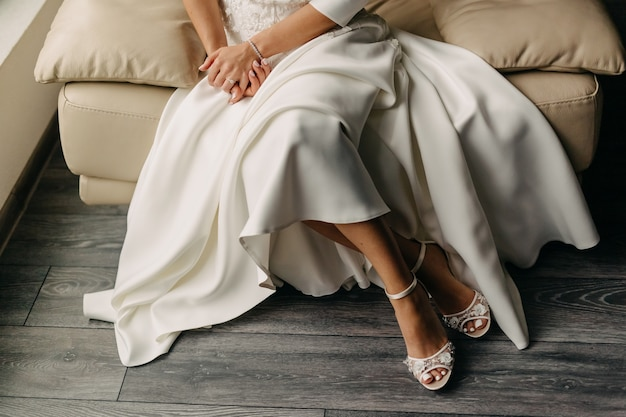 Sposa seduta su una sedia in pelle, close up di gambe