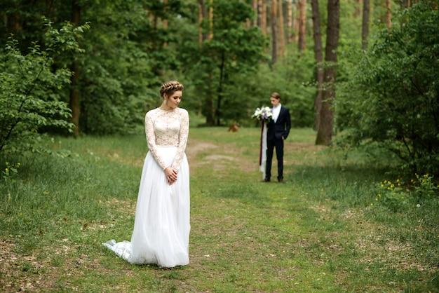 La sposa sorride nella foresta in primo piano. lo sposo tenendo il bouquet da sposa in sfondo sfocato.