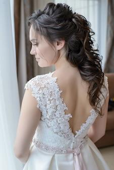 La sposa indietreggia e guarda fuori dalla finestra
