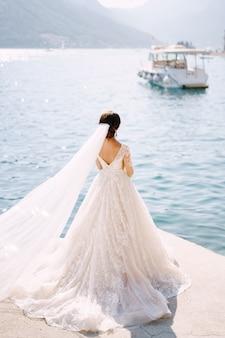 La sposa si trova sul molo della città di perast in montenegro e ammira le montagne e