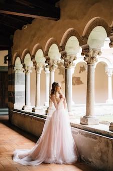 La sposa sta con le braccia incrociate sul petto su una loggia con colonne in un'antica villa sul lago