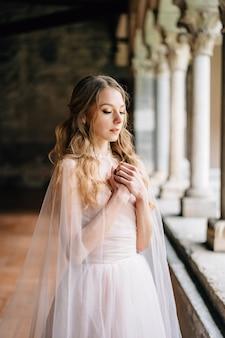 La sposa sta con le braccia incrociate sul petto su una loggia con colonne in un'antica villa