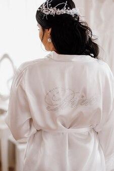La sposa sta con la schiena in pigiama di seta bianca
