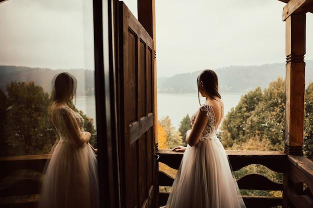 La sposa in un tenero abito da sposa sta sul balcone e guarda il lago