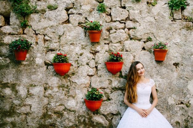 La sposa in tenero abito da sposa si trova vicino al muro di un antico edificio decorato con vasi di fiori a perast