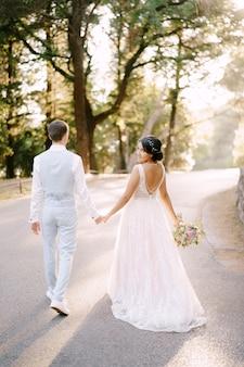 La sposa e camminano tenendosi per mano sulla strada tra gli alberi in un uliveto vista posteriore