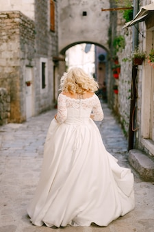 La sposa cammina lungo una bella stradina del centro storico di perast con case in mattoni
