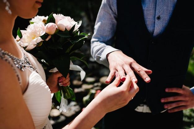 La sposa indossa l'anello d'oro sulla mano dello sposo. cerimonia matrimoniale.
