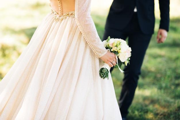 Sposa in abito da sposa azienda bouquet con lo sposo in background