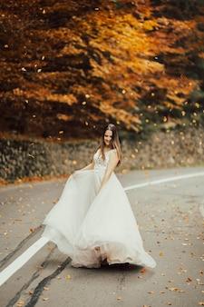 La sposa in abito da sposa sta girando sulla strada