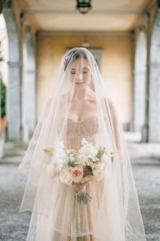 La sposa in abito da sposa e velo con un bouquet sta con gli occhi bassi su una vecchia terrazza