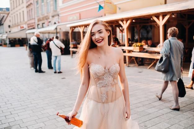 Una sposa in abito da sposa con i capelli lunghi e una bottiglia di bevanda nella città vecchia di wroclaw. servizio fotografico di matrimonio nel centro di un'antica città polacca a wroclaw, polonia.