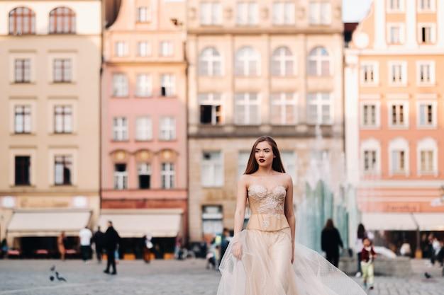 Una sposa in abito da sposa con i capelli lunghi nella città vecchia di wroclaw. servizio fotografico di matrimonio nel centro di un'antica città della polonia, wroclaw, polonia.