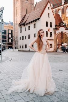 Una sposa in abito da sposa con i capelli lunghi nella città vecchia di wroclaw