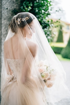 La sposa in un abito da sposa con un velo e un mazzo di fiori sta con la testa girata vicino al