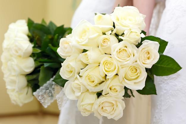 La sposa a un matrimonio con in mano un mazzo di fiori. la sposa in abito bianco a una cerimonia di matrimonio con un mazzo di rose.