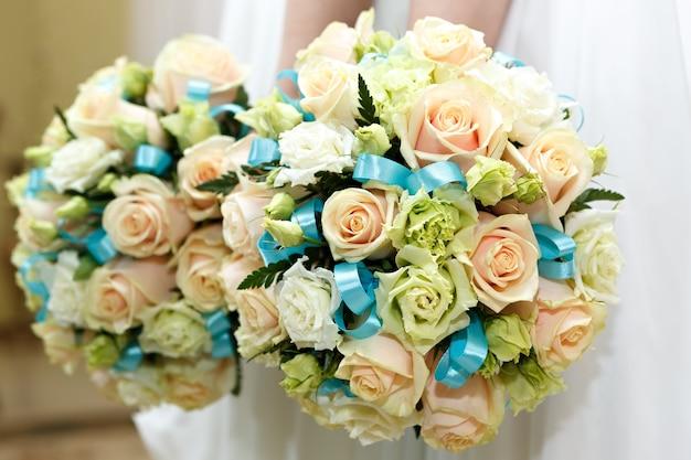 La sposa a un matrimonio con in mano un mazzo di fiori.