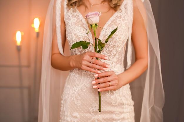 La sposa al matrimonio tiene una rosa tra le mani. bellissimo abito in pizzo