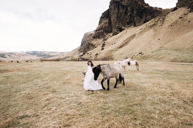 La sposa in abito bianco e un bouquet tra le mani accarezza un cavallo con una criniera nera in faccia