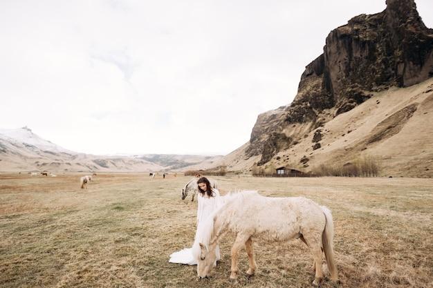 Sposa in un abito bianco in un campo con sessione fotografica di matrimonio di destinazione islanda cavalli con
