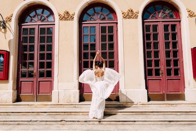 La sposa in un abito bianco che svolazza nel vento si trova di fronte alle alte porte di vetro di un antico