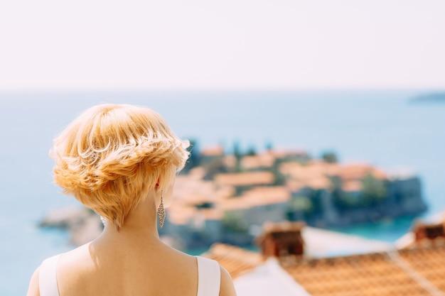 La sposa in abito bianco si alza e guarda l'isola di sveti stefan vicino a budva montenegro indietro