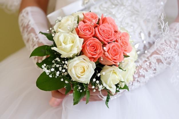 La sposa in abito bianco a una cerimonia di matrimonio con un mazzo di rose.