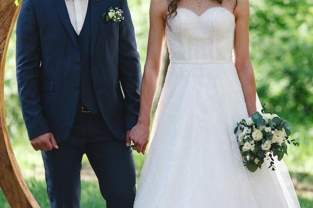 Sposa in abito bianco con un bellissimo bouquet e sposo che si tengono per mano all'aperto alla cerimonia di nozze