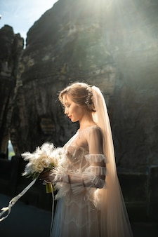 Una sposa in abito bianco con un mazzo di fiori sullo sfondo di montagne e gole della svizzera sassonia, germania, bastei.