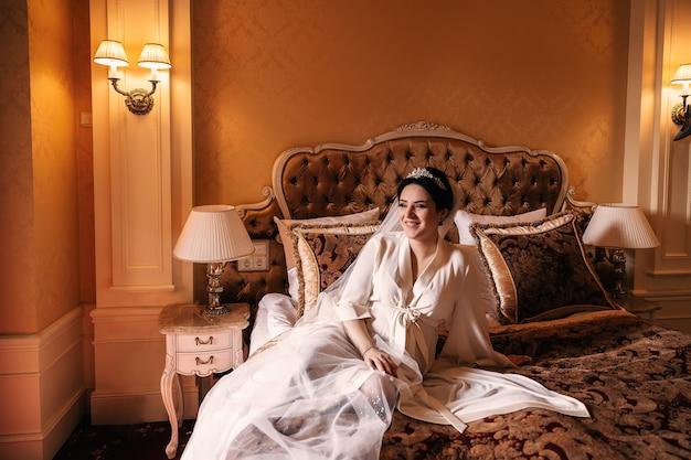 Sposa in vestaglia bianca che si siede sul letto chic e sul sorriso. camera da letto con letto chic.