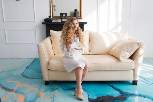 Sposa in vestaglia bianca sul divano