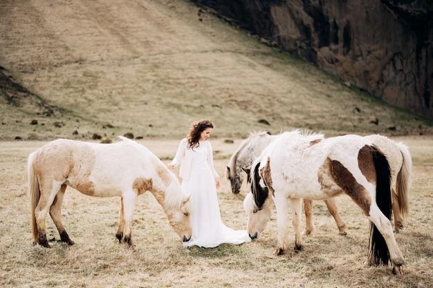 La sposa in abito bianco da sposa tra la mandria di cavalli cavalli leggeri sta annusando un vestito