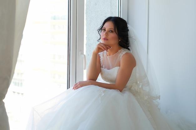 Una sposa in abito da sposa bianco in una stanza luminosa
