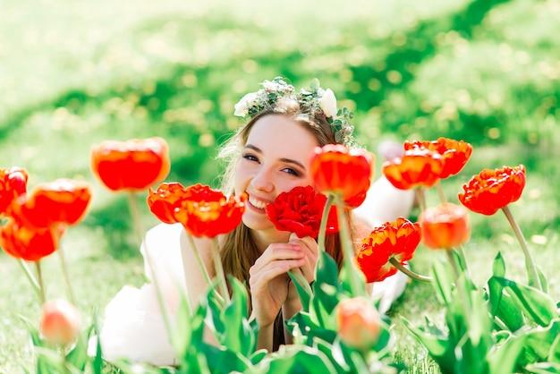La sposa in abito da sposa bianco è in possesso di un bouquet nel parco verde. matrimonio estivo in una giornata di sole.
